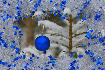 Blue Christmas ball hanging on tree branch in snow winter forest. The blue ball is hanging inside the box of tinsel