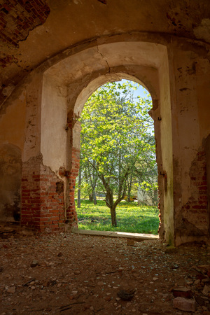 Belarus, the ruins of the Bernardine monastery of the 17th century. A fragment of a brick wall with a doorway. On the wall visible image. Abandoned collections.