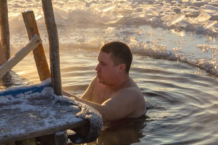 19.01.14 Polotsk Belarus. Swimming in the hole in the morning in the cold on the feast of the Baptism of the Lord. Men lead a healthy lifestyle and to do this in the winter swimming in the icy water.
