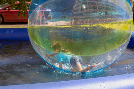 The little girl is inside a large transparent polyvinyl chloride ball. Children's summer attraction: zorb on the water surface. Extreme type of recreation on the water.