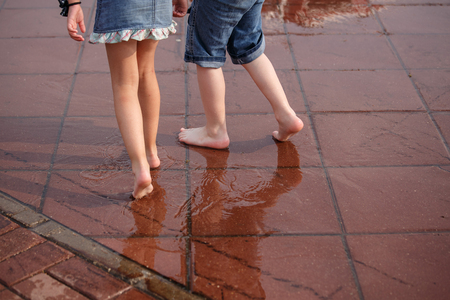 Children, boy and girl, running barefoot through puddles. The concept of happy childhood, summer vacation, friendship. Stockfoto