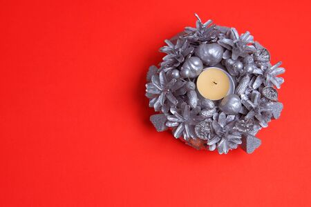 There is on the red background a beautiful round silver natural Christmas wreath-candlestick for design. Horizontal orientation, top view, copy space