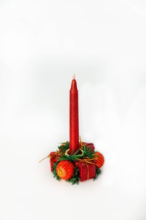 There is a beautiful red and gold Christmas or new year candle with a candlestick in the form of a wreath of balls and gifts. object on white background. for any design, for showcase