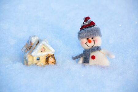 On the snow is a happy funny toy snowman and toy house. The snowman is wearing a fur hat and scarf. The concept of winter, Christmas, New year. Copy space. horizontal orientation.