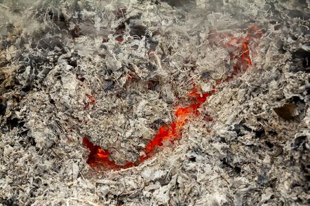mesmerizing glow glowing orange fire for any design. The gray background or texture is represented as ash on the edges and a smoldering flame inside. Horizontal background, selective focus. Stok Fotoğraf