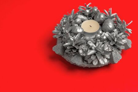 There is on the red background a beautiful round silver natural Christmas wreath - candlestick handmade festive for design. Horizontal orientation, side view, copy space