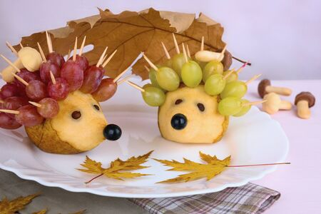 On a large white platter lie two cute handmade hedgehogs made from pears and grapes. Autumn decor with yellow leaves. Carving, handmade. Food photography, frontal location.