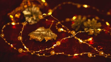There is an abstract blurred Burgundy dark Christmas holiday background with a garland of beads, cones and a Golden leaf. For holiday design. Selective focus.Copy space Stok Fotoğraf