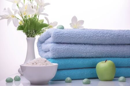 There are two blue Terry towels, white flowers in a vase, sea salt, a green candle and stones on a white background. Studio photography. The concept of relaxation purity freshness SPA.