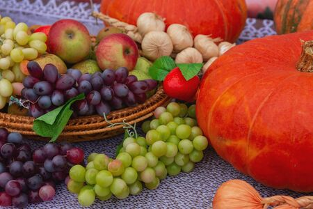 There are pumpkins, grapes, apples, onions and garlic lying on the table, destined for sale at the fair. Fresh vegetables and fruits and dummies. Autumn horizontal background.