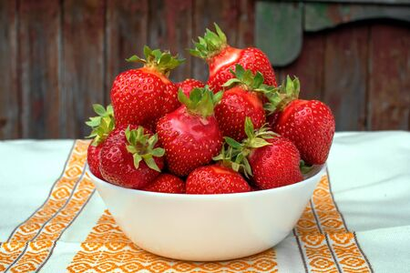There is a delicious large fresh bright red garden-grown strawberries Asia. A full bowl of strawberries stands on a white napkin with an ornament on a dark wooden background. Horizontal food backgroun Stok Fotoğraf