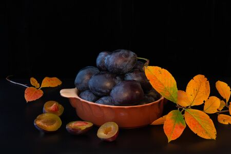 There are fresh delicious mouthwatering plums lying in a ceramic bowl and beautiful yellow leaves on a black background. Shot in a Studio on a black background with reflections. Copy space, horizontal arrangement.