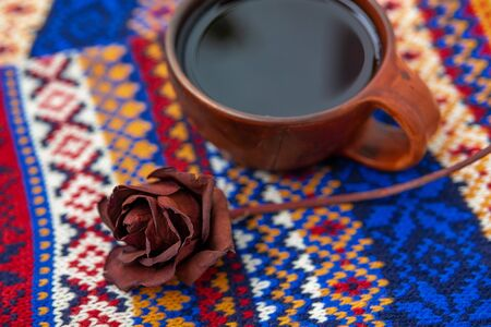 A dried red rose and a brown clay tea Cup are on a hand-knitted blue background. Cozy winter background: knitted scarf, lying on it a rose and a Cup of tea. Copy space. Selective focus, lens blur. Stok Fotoğraf