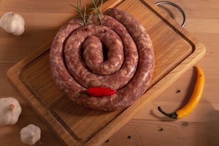 There is a delicious fresh traditional village sausage in a natural shell, rolled into a snail and lying on a wooden Board. Natural food: rustic sausage, garlic, hot pepper and rosemary.