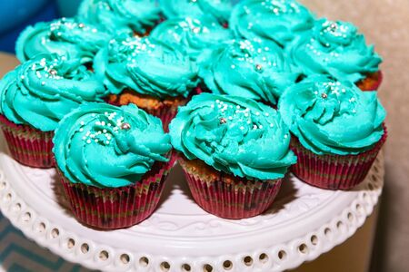 there are delicious tender fresh blue cupcakes, baked and decorated with air cream, lying on a white platter. Cakes prepared for a holiday, birthday. Stok Fotoğraf