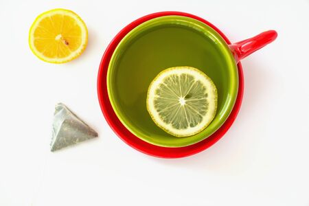 Bright ceramic green Cup filled with tea, lemon slice, tea bag and red saucer on white background. Green tea with lemon in a beautiful Cup, object. The view from the top