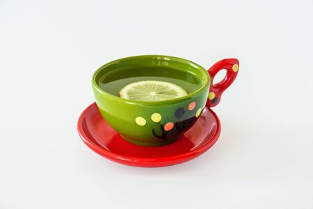 Bright ceramic green Cup filled with tea and red saucer on white background. Green tea with lemon in a beautiful Cup, object.