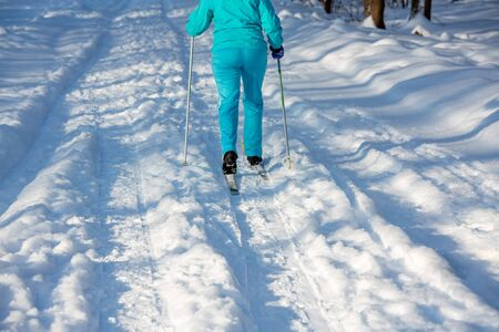Eine ältere Frau im Rentenalter fährt Ski für den Erhalt der Gesundheit. Skifahrer im blauen Anzug. Das Konzept eines gesunden aktiven Lebensstils Standard-Bild