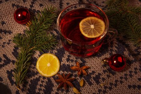 New year Christmas background. This is a glass Cup filled with a red drink with a slice of lemon, standing on a warm scarf, Christmas decorations, cardamom, star anise. Stok Fotoğraf