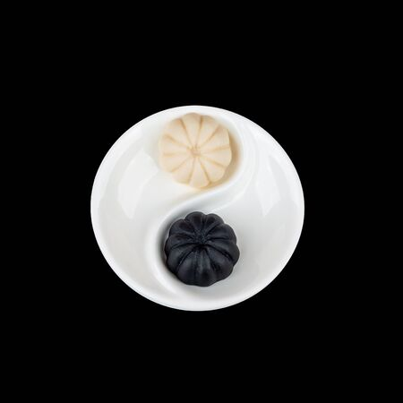 Natural fruit and milk marmalade Yin-Yang has a round shape and lies on a white menazhnitsey, divided among themselves. Selection on a black background.