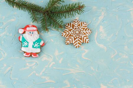 Christmas, new year background. On a blue-and-white background, imitating snow, lies a branch of spruce and ginger cookies in the form of snowflakes and in the form of Santa Claus.