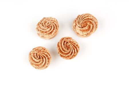 Four marshmallows, sprinkled with cinnamon and chocolate, lie on a white background. Top view isolated on white background.