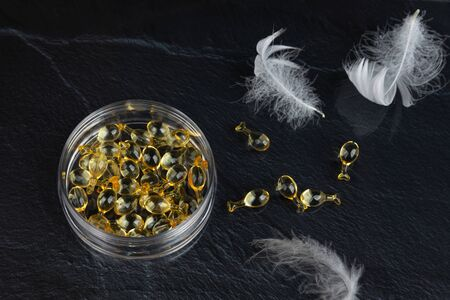 The restoring serum for the face in capsules is in a transparent jar and is scattered on a dark background. White feathers. The concept of healthy, elastic skin, lightness and beauty.