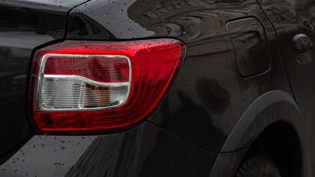 Detail on the car's rear light. Rear right light of a black car.