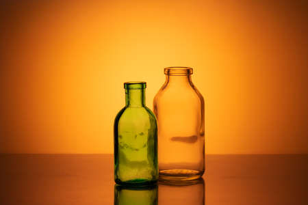 Old pharmacy glassware. Two old pharmacy glass bottles on an orange background in the background light.