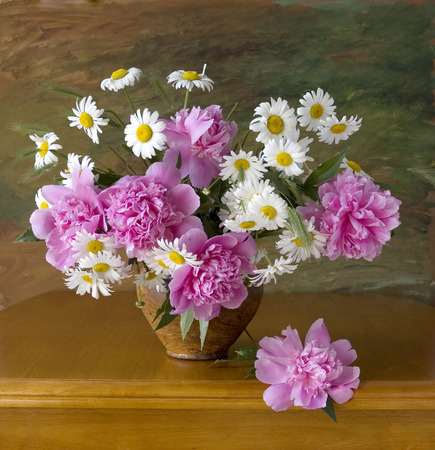 Still life with peonies and chamomiles on painting background photo