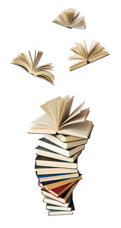 libros volando: Gran pila de libros con libros abiertos que vuelan lejos (concepto de la educación)
