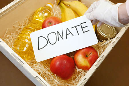 Donation food concept, wooden box with products, free food concept, fruits, oil in bottle and canned food, food drive