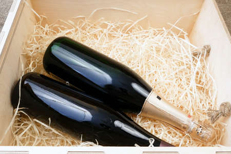 glass and bottle of expensive elite wine in a wooden box with shavings, wine tasting, online order and delivery wine in coronavirus time, internet wine shops concept