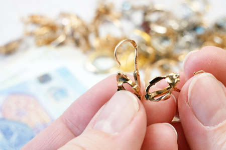 jewelry scrap of gold and silver and money, pawnshop concept jeweler looking at jewelry through magnifying glass, jewerly inspect and verify Banque d'images