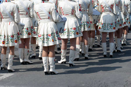 group of drummer girls in white Ukrainian costumes with traditional red ornament, Marching girl band drummers perform, drummers parade