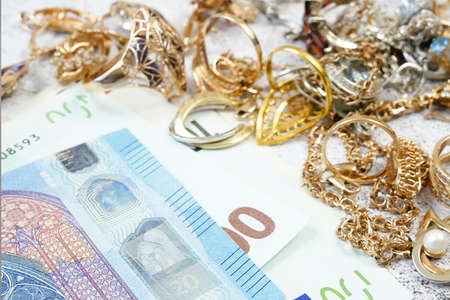 jewelry scrap of gold and silver and money, pawnshop concept jeweler looking at jewelry through magnifying glass, jewerly inspect and verify