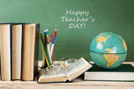 Book pile with apple, globe, pencils and sharpener on the school blackboard. Teacher's day concept