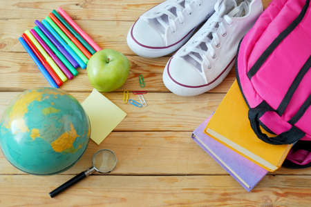 Back to school, books pile, pencils, apple, globe and apple over chalkboard background