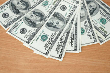stack of usa dollars on wooden background,