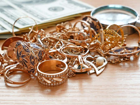 jewelry scrap of gold and silver and money, pawnshop concept jeweler looking at jewelry through magnifying glass
