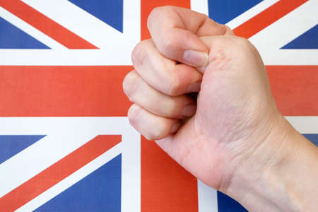 clenched fist against the background of the flag in britain, protests in united kingdom