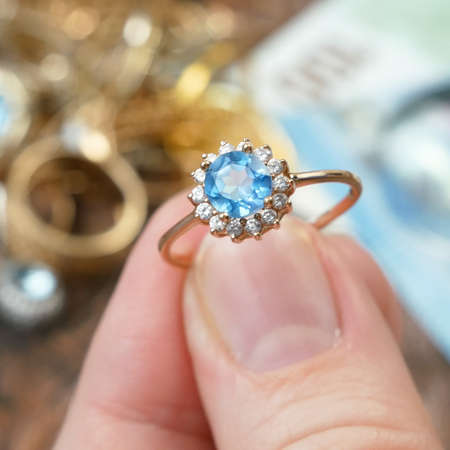 hand takes ring with big topaz stone and many diamonds, jewelry scrap of gold and silver and money, pawnshop concept, closeup