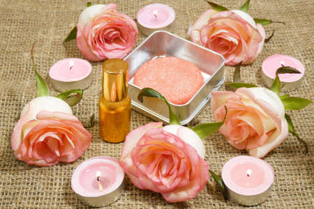 Bottle of perfume, soap with pink roses flowers and candles, closeup Banque d'images