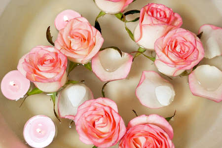 Pink rose, candles and petal floating water in bowl. Relaxing Hand Spa closeup Archivio Fotografico
