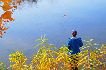 Autumn Fishing on a river. Young man relaxing and fishing, Amateur angler fishing on the autumn river, many alive fish in basket 免版税图像