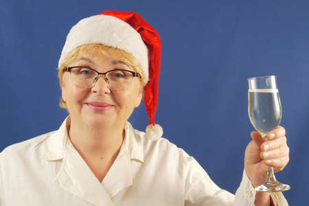 Merry Christmas and Happy New Year! woman doctor celebrating winter holidays at work in uniform and Santa Claus hats drinking champagne in glass. Wealth and health in new year, closeup