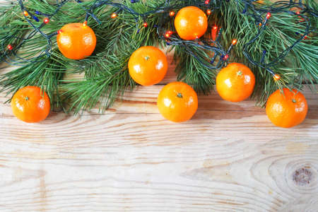 tangerines, candle, lights, stars on a wooden background. xmas and new year decor. Christmas card. Merry Cristmas and Happy new year, copy space
