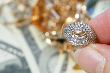 golden ring in hand, jewelry scrap of gold and silver and money, pawnshop concept jeweler looking at jewelry through magnifying glass, jewerly inspect and verify