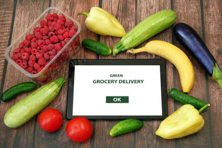 Organic Vegetables and fruits in cotton bag and tablet pc, online market, green grocery delivery at home concept, buy online concept Фото со стока