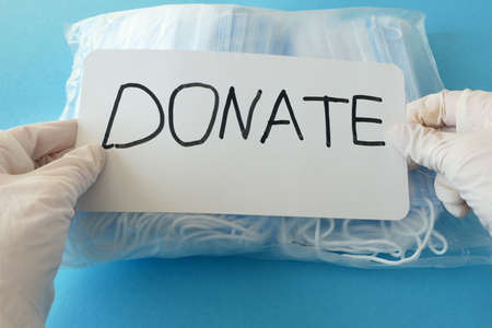 hand in gloves, medical packing face masks and nameplate donation on blue background